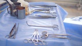 De chirurgische instrumenten liggen op een het ziekenhuislijst die met beschermend materiaal behandeld is stock footage