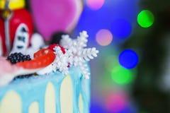 De chocolade, de snoepjes en de sneeuwvlokken van het cakedecor op een achtergrond van gekleurde lichten Royalty-vrije Stock Afbeelding