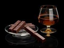 De chocolade en de cognac in glaswerk het zijn geïsoleerd op zwarte stock afbeeldingen