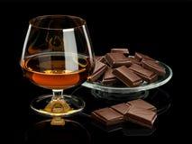 De chocolade en de cognac in glaswerk het zijn geïsoleerd op zwarte royalty-vrije stock afbeeldingen