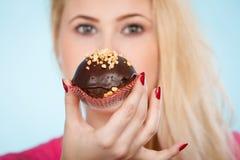 De chocolade van de vrouwenholding cupcake ongeveer aan beet royalty-vrije stock foto's