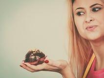 De chocolade van de vrouwenholding cupcake ongeveer aan beet royalty-vrije stock afbeelding