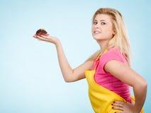 De chocolade van de vrouwenholding cupcake ongeveer aan beet royalty-vrije stock afbeeldingen
