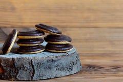De chocolade verglaasde koekjesstapel op een houten achtergrond met exemplaarruimte voor tekst Ronde koekjes in het donkere suike Royalty-vrije Stock Foto
