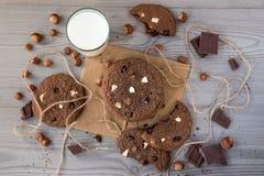 De chocoladekoekjes met hazelnoten, witte chocolade en donkere chocolade op perkament en glas melk, houten vlakke achtergrond, le Royalty-vrije Stock Fotografie