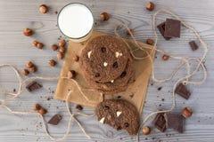 De chocoladekoekjes met hazelnoten, witte chocolade en donkere chocolade op perkament en glas melk, houten vlakke achtergrond, le Stock Foto's