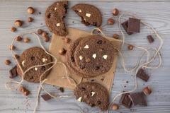 De chocoladekoekjes met hazelnoten, witte chocolade en donkere chocolade op perkament, houten vlakke achtergrond, leggen Royalty-vrije Stock Afbeeldingen