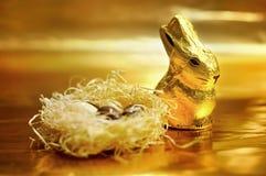De chocoladekonijn en eieren van Pasen op gouden achtergrond Royalty-vrije Stock Afbeeldingen