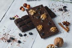 De chocoladereep met verschillende bessen wordt gevuld en de noten liggen oude wo die Royalty-vrije Stock Foto's