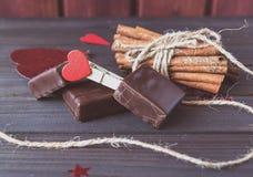 De chocoladerepen met pijpjes kaneel en de doek spelden en koord op de Dag van houten plankenstvalentine Stock Foto