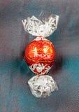 De chocoladetruffel van Lindtlindor op een zijde van de kameleonluxe backgr Royalty-vrije Stock Afbeeldingen