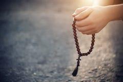De Christen houdt in zijn handen houten rozentuinen stock afbeeldingen