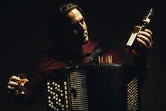 De chromatische harmonikaspeler met een gedistilleerde drank stock fotografie