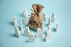 De cijfers van mensen worden getrokken aan zak geld en rijkdom royalty-vrije stock fotografie