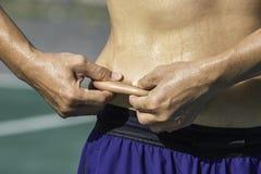 De cintura gorda de la piel del apret?n del hombre de la mano exceso fotos de archivo