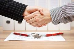 De cliënt en de agent zijn handenschudden over onroerende goederencontract en k royalty-vrije stock afbeeldingen