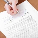 De cliënt ondertekent een overeenkomst door zilveren pen Stock Fotografie