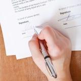 De cliënt ondertekent een overeenkomst door zilveren pen Stock Foto