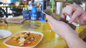 De cliëntfoto's hielden van de schotel op een mobiele telefoon Neem een foto van tom yam Thaise soep in een restaurant met mobiel Royalty-vrije Stock Afbeeldingen
