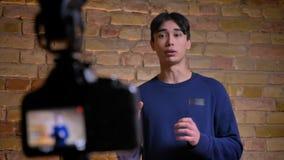 De close-up concentreerde spruit van camera die jong Koreaans mannetje videoblogger het sprekende en gesturing opnieuw concentrer stock video