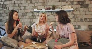 De close-up in een moderne slaapkamer jonge aantrekkelijke dames die pizza eten die sommige dranken drinken en heeft het interess stock footage