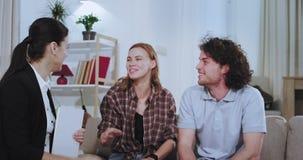 De close-up in een woonkamer charismatisch paar maakt hun huisagent behandelen om een huis te huren zij het schudden handen met stock footage