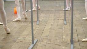 De close-up, Jonge ballerinabenen in balletschoenen, pointes, in beige maillotten, voert oefeningen dichtbij staaf, op oud uit stock video