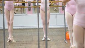De close-up, Jonge ballerinabenen in balletschoenen, pointes, in beige maillotten, voert oefeningen dichtbij staaf, op oud uit stock footage