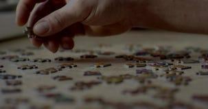 De close-up van bemant handen assemblerend raadsel stock video