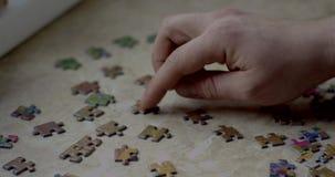 De close-up van bemant handen assemblerend raadsel stock footage
