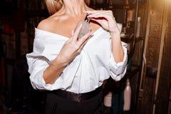 De close-up van blonde vrouw draagt een wit overhemd en houdt haar hand op de fles, flessenparfum, geur stock afbeelding