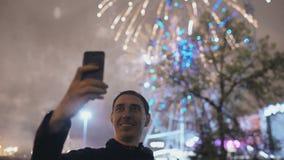 De close-up van de jonge vrolijke en mens die selfie stelt in openlucht voor met vuurwerk op smartphonecamera letten op maken stock videobeelden