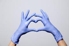 De close-up van dient latex rubber medische purpere die handschoenen in in een hartteken worden gevouwen Geïsoleerdj op witte ach stock afbeelding