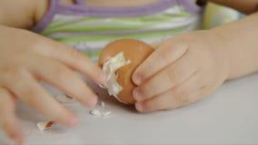 De close-up van een kleine meisjeszitting als kinderen` s voorzitter maakt shell met een gekookt kippenei schoon en eet het stock video