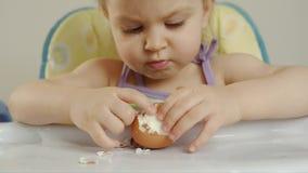 De close-up van een kleine meisjeszitting als kinderen` s voorzitter maakt shell met een gekookt kippenei schoon en eet het stock videobeelden