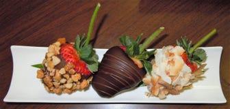 De close-up van een vertoning van individuele ondergedompelde Aardbeien met Macadamia noten, chocolade en kokosnoot schilfert af royalty-vrije stock foto