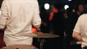 De close-up van de handenslagwerker het spelen op een drumstel bij een rotsoverleg stock videobeelden