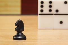 De close-up van het schaakpaard op een achtergrond van dominoe stock foto