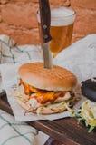 De close-up van huis maakte hamburger met kip, tomatensaus, ketchup en een glas bier met een mes wordt op weinig wordt geplakt ge Stock Foto's
