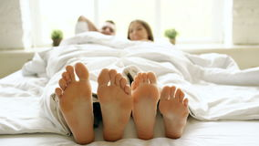 De close-up van jong mooi en het houden van paarspel en danst hun voeten onder deken terwijl kielzog omhoog in bed in ochtend stock video