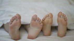 De close-up van jonge mooi en het houden van paaromhelzing en speelt hun voeten stock videobeelden