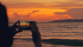 De close-up van jonge toeristenvrouw fotografeert oceaanmening met smartphone tijdens zonsondergang bij strand stock footage