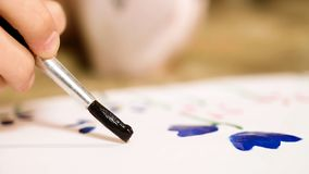 De close-up van kindhand die zorgvuldig bloeit met gouache, creativiteit, talent trekken royalty-vrije stock foto