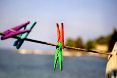 De close-up van kleurrijke wasknijpers hing op een kabel van de wasserijlijn op een blauwe kustachtergrond stock foto's
