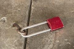 De close-up van oud gekrast rood fietsslot maakte aan een oogje in ruw beton vast - selectieve nadruk royalty-vrije stock afbeeldingen