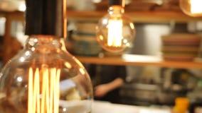 De close-up van retro gloeilamp die een donker geel licht in de achtergrondmensengang op een achtergrond van het koffierestaurant stock videobeelden