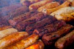 De close-up van sommige vleesvleespennen die in een barbecue worden geroosterd Geroosterde vleesvleespennen, barbecue Stock Afbeeldingen