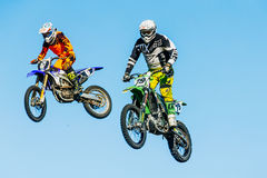 De close-up van twee motorrijders springt van een berg op achtergrond van blauwe hemel Stock Fotografie
