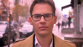 De close-up van de volwassen Kaukasische mens zag aan camera onder ogen vooruit kijkend in glazen die zich op de straat door weg  stock videobeelden