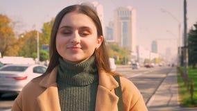 Is de close-up vrij Kaukasische vrouw rechtmaakt haar haar en het glimlachen met natuurlijk gezicht bij camera terwijl status op  stock video